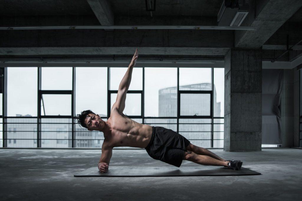 Homme faisant une planche latérale avec extension du bras opposé.