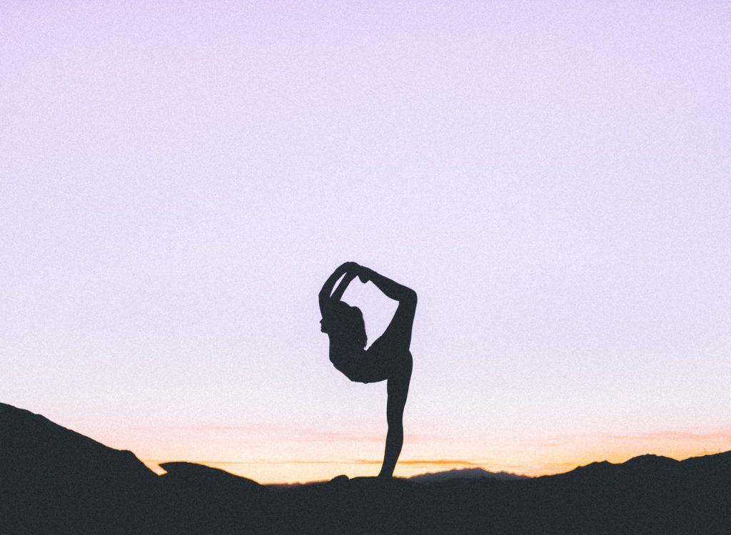 Ombre d'une femme faisant du yoga devant un ciel embrasé par le soleil couchant.