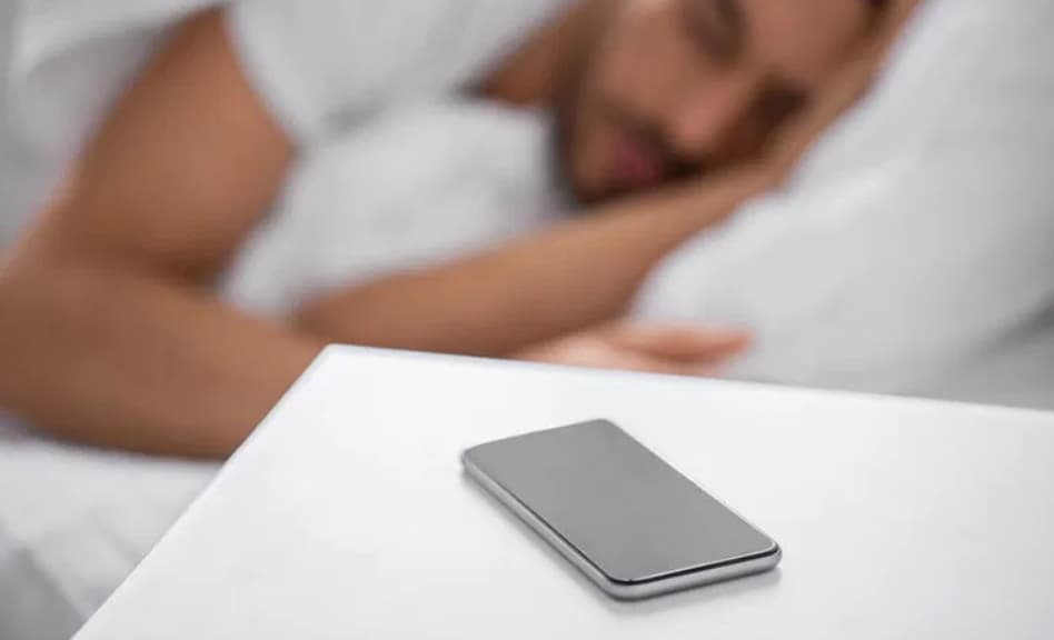 Téléphone sur la table de nuit - premier réflexe de la journée